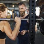 Donna che fa squat con personal trainer